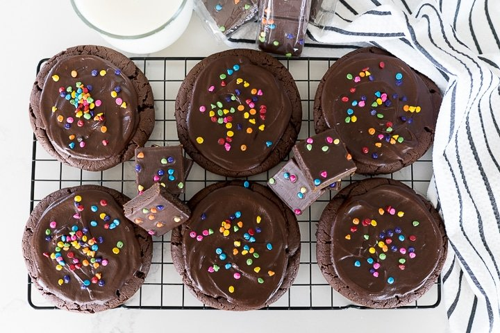 Chocolate brownie cookies on a cookie cooling rack with cosmic brownies by them