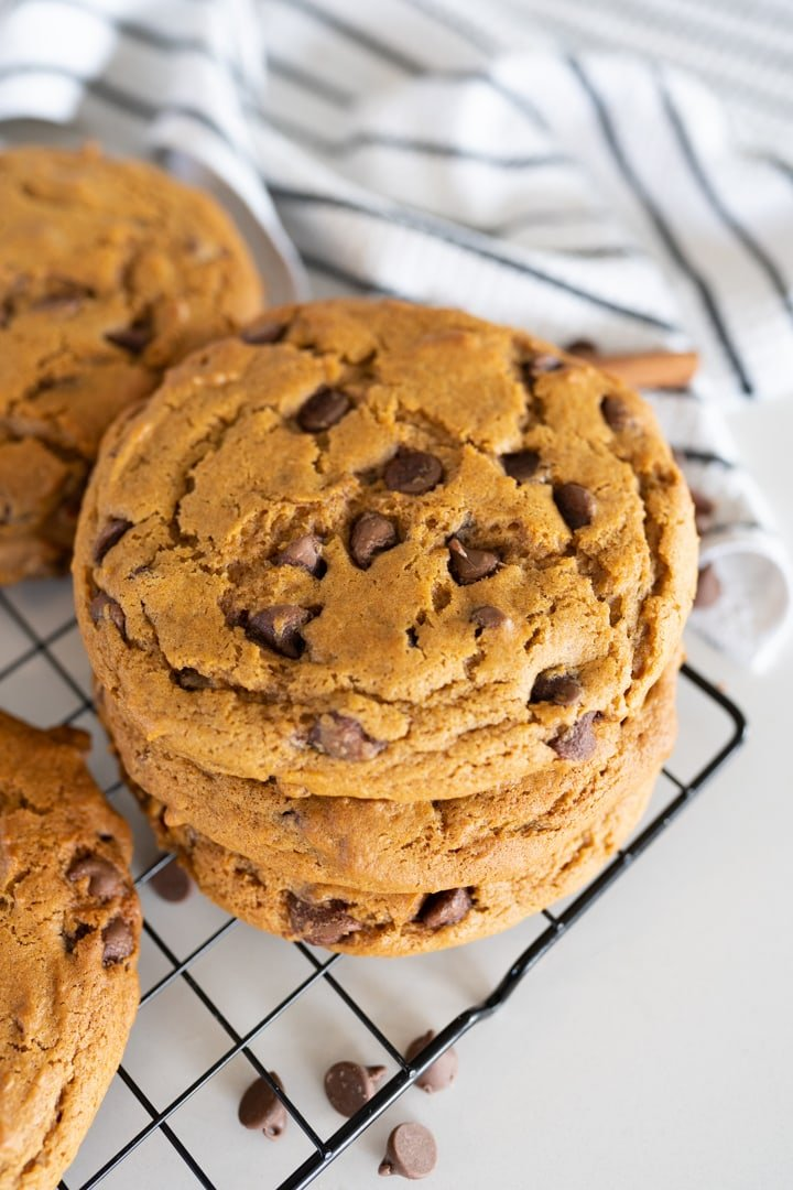 large chewy pumpkin chocolate chip cookies stacked on a cookie cooling rack