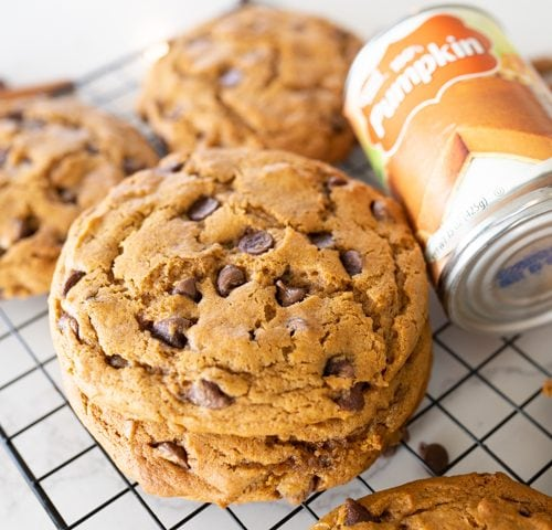 Crumbl pumpkin chocolate chip cookies on a cookie cooling rack with a can of pumpkin