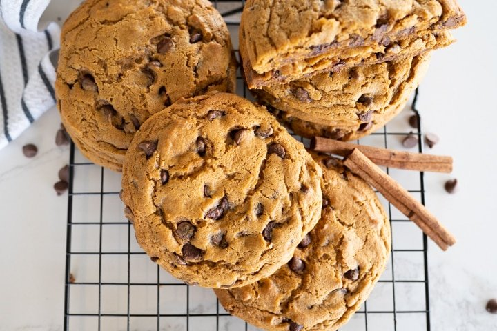large pumpkin chocolate chip cookie on a cookie cooling rack