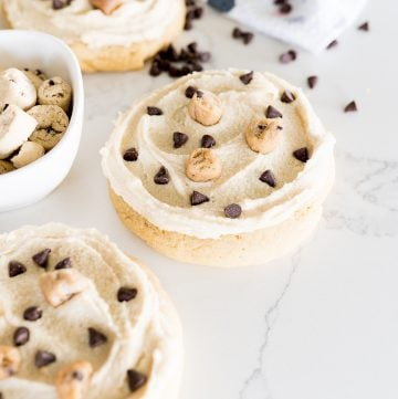 cookie dough cookie with cookie dough bits on top on the counter