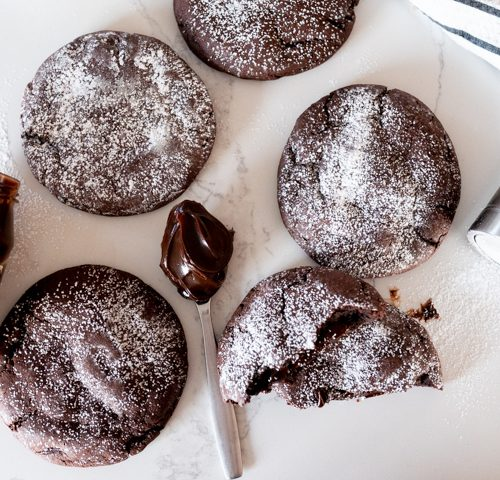 molten lava cookies on a counter with hot fudge sauce